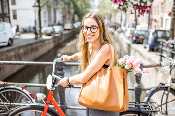 Portrait of a young beautiful woman with red bicycle holding bag and bouguet of tulips standing on the bridge in Amsterdam old city