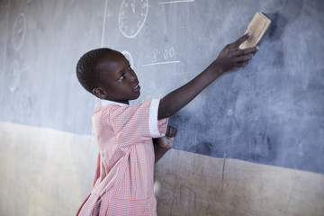 School girl cleaning chalkboard in classroom. Kenya Africa.