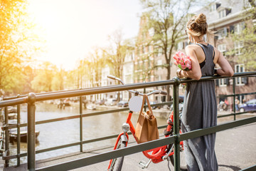 Poster Amsterdam Young and beautiful woman standing with bicycle and flowers on the bridge over the water channel in Amsterdam city