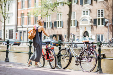 Young and beautiful woman with bag and flowers walking with bicycle on the water channel in Amsterdam city