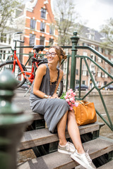 Portrait of a young happy woman sitting with bouguet of pink tulips on the bridge in Amsterdam city