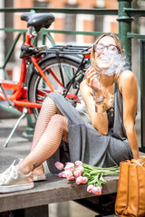 Young smiling woman smoking a cigarette sitting with flowers and bicycle on the bridge in Amsterdam city