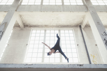 Sportswoman doing flip in urban building