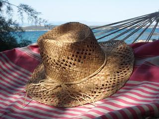 Urlaub am Meer: Strohhut, Strandtuch, Hängematte