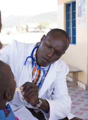 Doctor examining child (female) from Maasai tribe. Kenya, Africa.