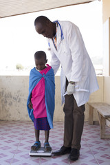 Doctor examining young girl from Maasai tribe. Kenya, Africa.
