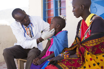 Doctor examining young girl from the Maasai tribe. Kenya, Africa.