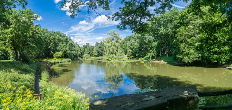 Panorama of a public park in the city. Sunny picture with trees and a lake. Luisenhain, Bamberg.