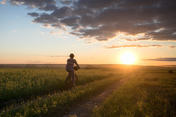 Girl on a bicycle in a field on the road against the sunset background