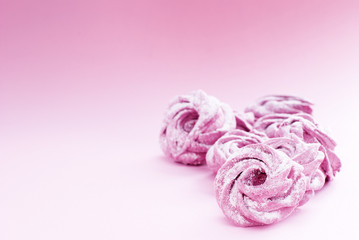 delicate pink marshmallow in powdered sugar, on a pink background