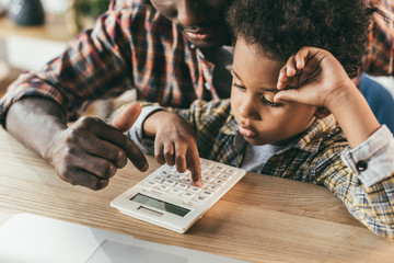 father and son with calculator