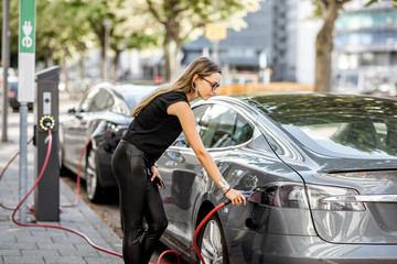 Young woman in black clothes putting connector into the electric car outdoors on the street in Rotterdam city