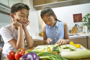 Siblings cutting vegetables in the kitchen
