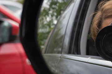 A photographer takes pictures from a car window. View through a car's side mirror.