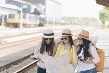 Group of beautiful traveler woman (friends) searching right direction at train station.Asian Backpackers pointing and planning holiday vacation with location map.