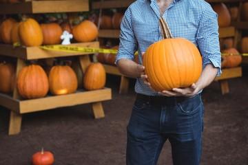 Man holding pumpkin at supermarket