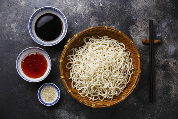 Raw Udon noodles in bamboo basket with sauces and sesame on dark background