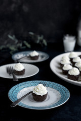 Brownie Bites with Orange Blossom Mascarpone Frosting served with milk.  Photographed on a dark blue background.
