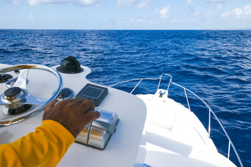 Hand of captain on  the speed switch and steering wheel of fishing motor boat in the blue ocean during fishery day