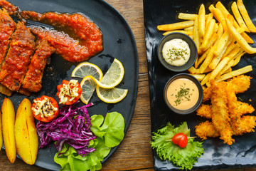 Pork Spare Ribs Barbecue with fried potato and Fish and Chips with salad and wasabi sauces in black ceramic dish on wooden table