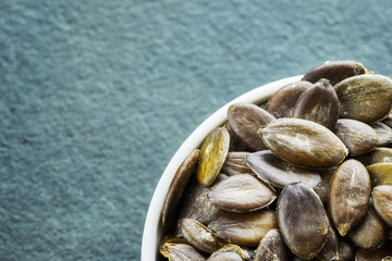 Close up picture of pumpkin seeds in a bowl, shallow depth of field, space for text.