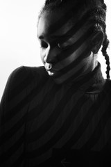 Creative light stripes from a projection on beautiful woman with dark skin