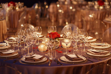 Sparkling glassware stands on dinner table decorated with red roses