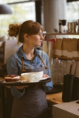 Waitress holding cup cake on tray