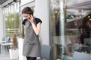 Female owner talking on smart phone