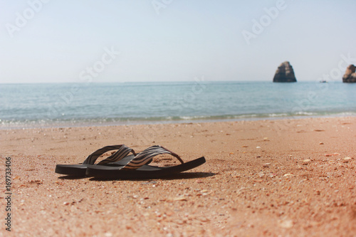 48ad5a87d Flip flops on empty sandy beach with cliff rocks on background. Shoes of  single person isolated at popular summer vacation stop on early morning.