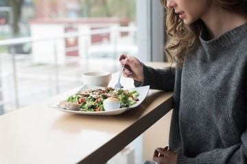 mid section of woman having salad in cafe