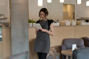 Female owner using tablet computer in cafe