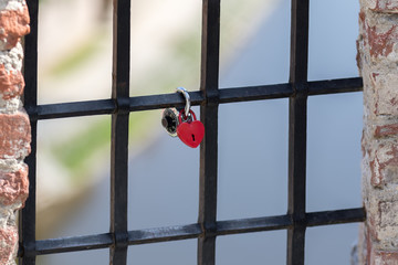 Cesky Krumlov, Czech Republic - August 17, 2017: Red heart-shaped padlock is chained to an inferno on the river in the historic city center
