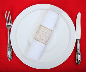 Formal table setting on red tablecloth