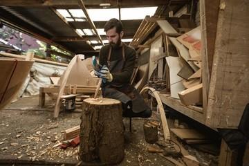 Carpenter cutting wooden log