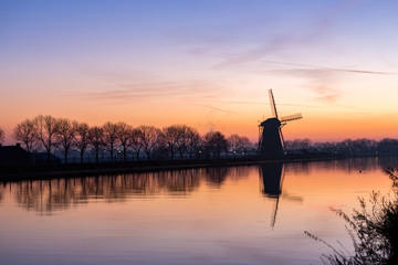 Windmill with reflection at sundown in Nieuwe Wetering
