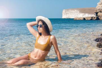 Beautiful girl in bikini, glasses and hat in clear sea water