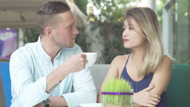 Loving couple chatting while drinking coffee