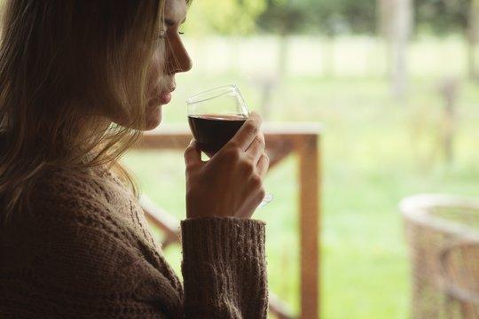 Thoughtful woman having glass of wine