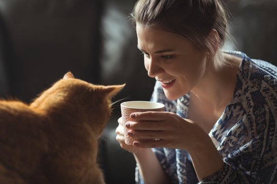 Woman having cup of coffee while playing with cat