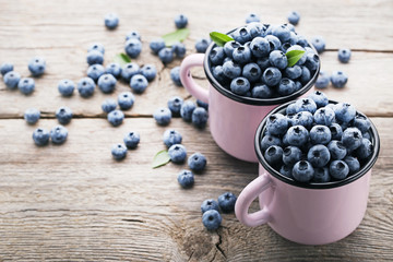 Ripe blueberries in pink mugs on wooden table