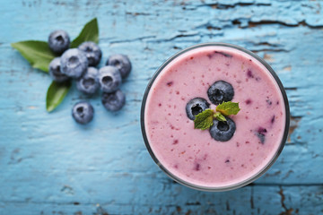 Wall Mural - Fresh blueberry smoothie in glass on blue wooden table