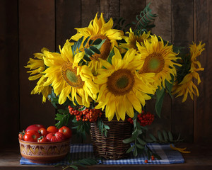 Sunflowers and tomatoes. Rustic still life of flowers and vegetables.