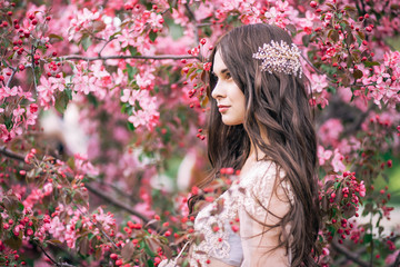 beautiful cute brunette girl bride in boudoir lace transparent dress, with decoration on the hair, near the tree blossoms with pink flowers, profile, horizontal, garden