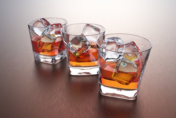 Three glasses of whiskey with ice cubes on a metal table.