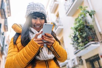 Tourist asian woman using mobile in european street.