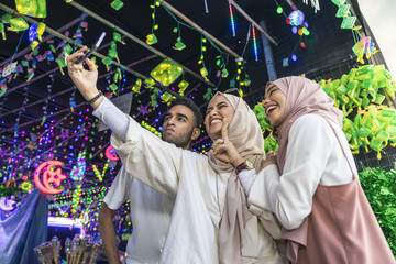 A group of friends taking a selfie against the hari raya decorations.