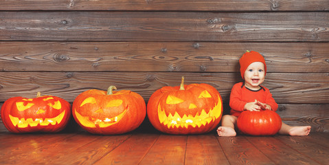 happy baby in costume for Halloween with pumpkins on wooden background