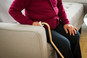 Mid section of senior woman holding walking cane