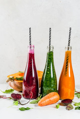Vegan diet food. Selection colorful fresh organic vegetable smoothies with autumn vegetables: beetroot, pumpkin, carrot, leafy vegetables. In bottles, with straws, white marble table. Copy space